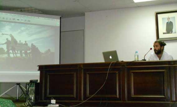 Andrés Martínez, en un momento de su conferencia, junto a una de las imágenes expuestas. Fotografía de Sergio Jorge.