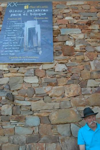 El pintor Sendo junto a un cartel de su exposición en Castrillo de los Polvazares (León). © Fotografía: Eloy Rubio Carro.