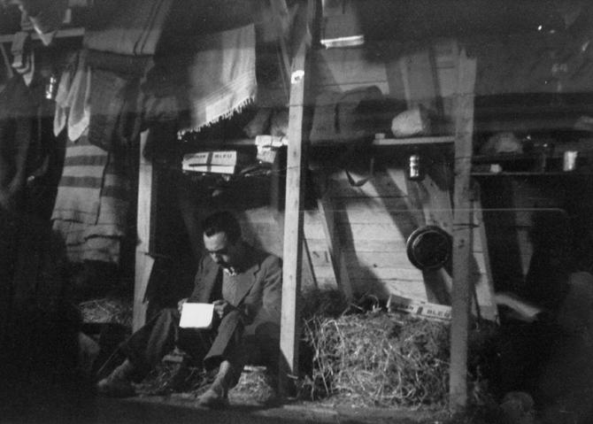 """""""Un refugiado lee una carta en su cubículo"""". © Ministerio de Cultura de España. Centro Documental de la Memoria Histórica. Fondo Histórico Agustí Centelles i Ossó. [""""Esta fotografía se suministra exclusivamente para la información cultural de la exposición, no se puede almacenar en forma alguna ni ceder a terceros""""]."""