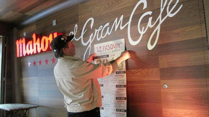 El artista Juan Rafael colocando uno de los carteles hechos a mano en El Gran Café. © Fotografía: E. Otero.