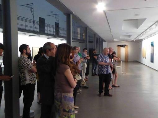 El comisario de la muestra, Carlos Trigueros, en el centro, durante una visita guiada por la exposición.