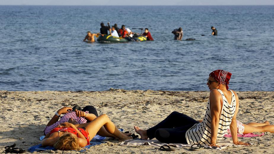Turistas tumbados en la playa mientras inmigrantes y refugiados de Siria y África llegan en lanchas neumáticas a la isla griega de Kos, tras haber cruzado parte del Mar Egeo entre Turquía y Grecia. © REUTERS/ Yannis Behrakis.