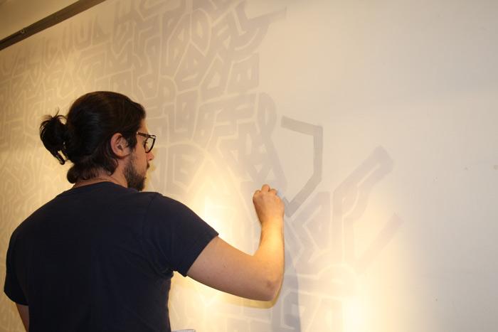 Lio pintando el laberinto de las paredes sobre las que ha colgado los cuadros. Foto: Ana Blanco.