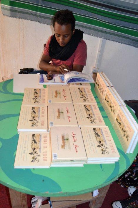 """Joven saharaui muestra al público el libro del pintor Javier de Blas """"Viajero en Tindouf"""". ARTifariti 2015. Fotografía: Antonio Muñoz."""