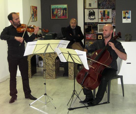 Jular, en la galería Ármaga, escuchando tocar a David de la Varga y Pelayo Tahoces.